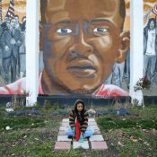 A young woman sits beneath a mural of Freddie Gray in Baltimore (AP Photo/Patrick Semansky)