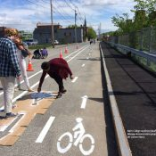 College students install a protected bikeway demonstration project in Lewiston, Maine (Credit: Street Plans)